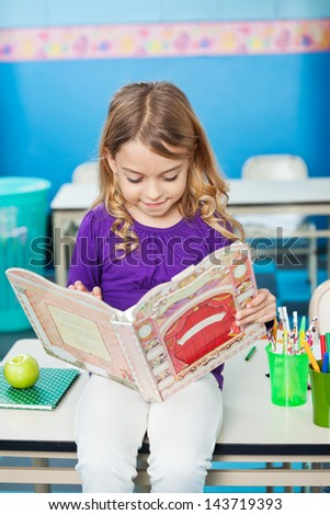 Little girl reading book while sitting on desk in classroom - stock photo