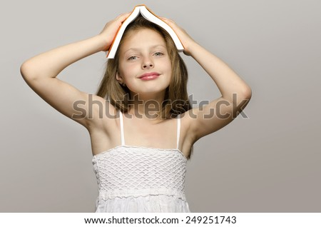Little girl reading some books, kid learning, child studying, child having fun with a book. Girl with a book on her head smiling and thinking, preparing for school - stock photo