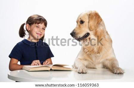 little girl reading with her golden retriever - stock photo