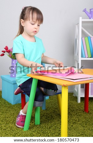Little girl reads book sitting at table in room - stock photo