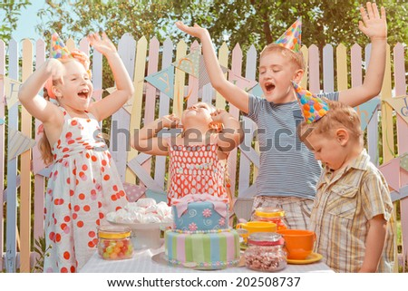 Little girl rejoice  in her birthday round about her very emotional friends  - stock photo