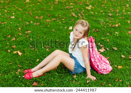Little girl resting in a park after school - stock photo