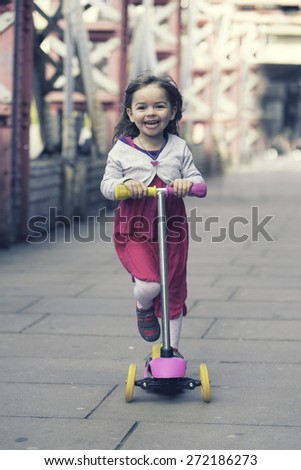 Little girl ridding scooterin the middle of a bridge, London - stock photo