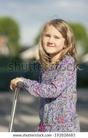 Little girl ride the scooter in the park  - stock photo