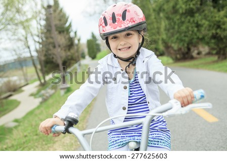 Little girl riding a bike - stock photo