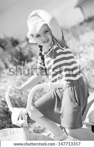 Little girl riding a bike. Retro, black and white. - stock photo