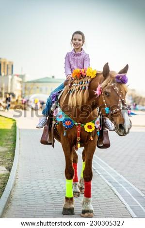 Little girl riding festive horse in summer city Park. - stock photo