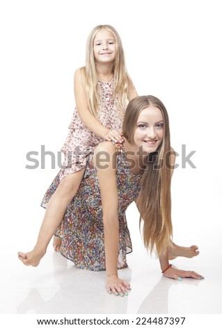 Little girl riding her sister. Isolated on the white background. - stock photo