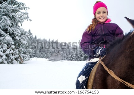 Little girl riding horse in winter - stock photo
