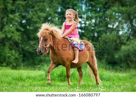 Little girl riding little pony - stock photo