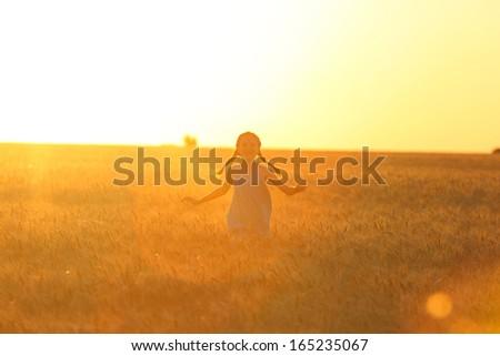little girl running at the orange evening wheat field   - stock photo