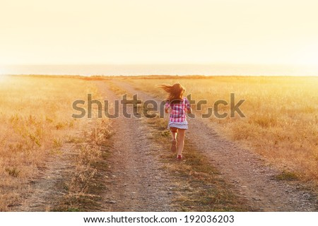 Little girl running down the road at sunset. carefree. inspiration. children outdoors - stock photo