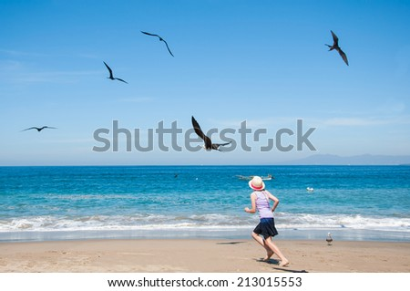 Little girl running in beach with seagull - stock photo