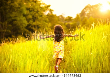 Little girl running on meadow with sunset - stock photo
