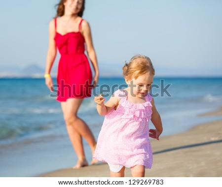 Little girl running on the beach - stock photo