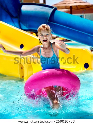 Little girl running with inflatable ring. - stock photo