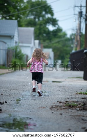 Little girl runs away from the camera, splashing through puddles in an alley - stock photo