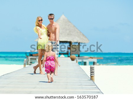 Little girl runs toward her parents on the bridge. Family of three having tropical vacation - stock photo