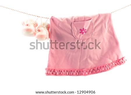 Little girl's clothes and slippers hanging on a rope. Copy space - stock photo