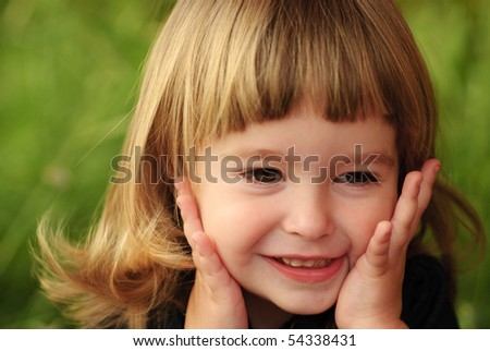 Little girl's face with hands and smile. Close up soft portrait on nature - stock photo