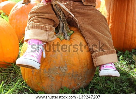 Little girl's legs dangling from her seat on a large orange pumpkin she singled out to take home from the local pumpkin patch. - stock photo