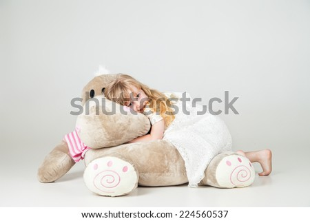 Little girl sat with cuddly toy and smile over white background - stock photo