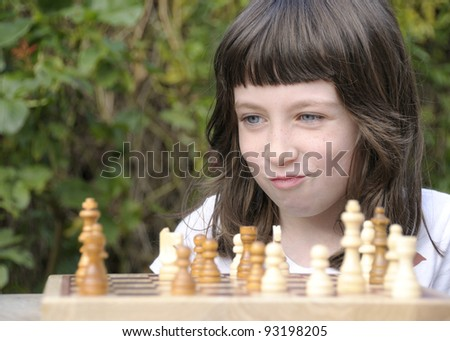 Little girl satisfied with her next move in a game of chess. - stock photo