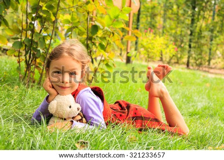 Little  girl seats on the meadow in autumn sunny day, embracing teddybear - stock photo