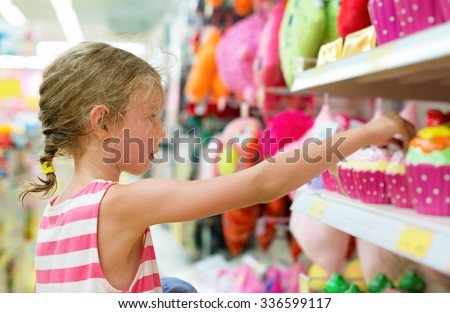 Little girl selecting toy on shelves in supermarket. - stock photo