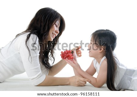 Little girl sharing grapes with mom - stock photo