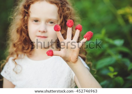 Little girl showing five finger with raspberry. Focus on a palm. Healthy, medical and happy childhood concept. - stock photo