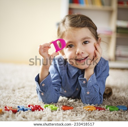 Little girl showing letter D learning the letters at home - stock photo