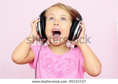 little girl singing in headphones - stock photo