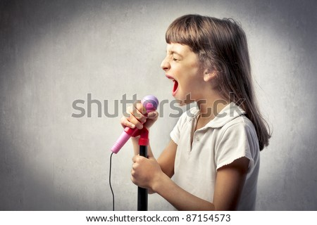 Little girl singing into the microphone - stock photo