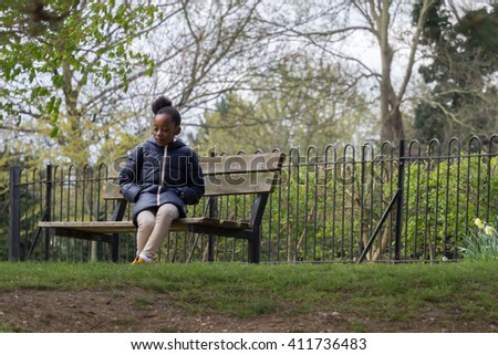 Little girl sits alone on a park bench - stock photo