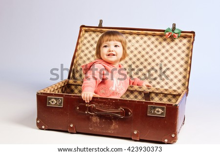 Little girl sits in a suitcase on light background - stock photo