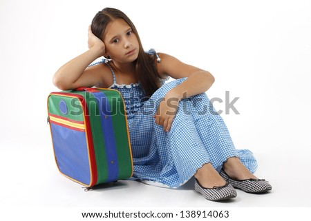 little girl sits leaning on suitcase and waiting to embark on the journey - stock photo
