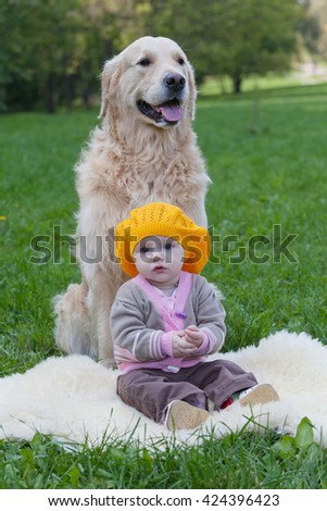 little girl sits near a big dog  golden retriever - stock photo