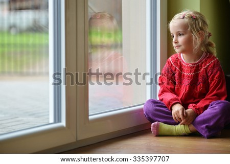 little girl sits near window, portrait   - stock photo