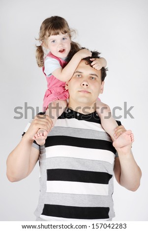 Little girl sits on shoulders of her father and holds his hair on grey background. - stock photo