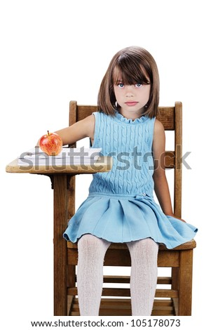 Little girl sitting at a school desk with apple and books. Isolated on a white background with clipping path included. - stock photo