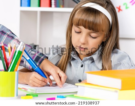Little girl sitting at desk in the classroom, doing homework at the table.  - stock photo