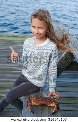 Little girl sitting at table by sea, with alive Norwegian Brown crab, Cancer pagurus,  edible crab, crab Tourteau on bench, gesturing thumb up, outdoors - stock photo