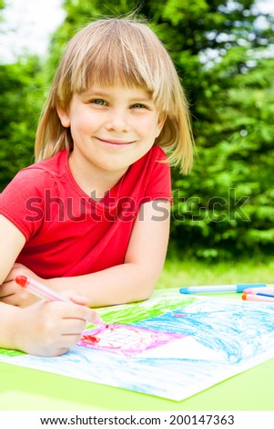 Little girl sitting at table drawing a house outdoors - stock photo