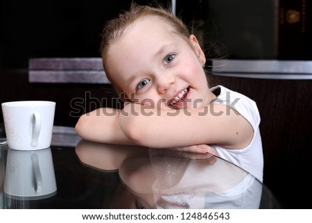 Little girl sitting at the table - stock photo