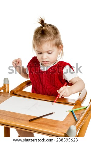 Little girl sitting at the table and draws pencils closeup isolated on a white background - stock photo