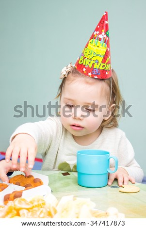 Little girl sitting at the table in her birthday - stock photo