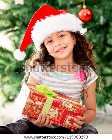 Little girl sitting by the tree holding a Christmas gift - stock photo