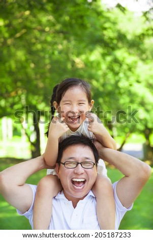 little girl sitting father shoulder and make a funny facial expression - stock photo