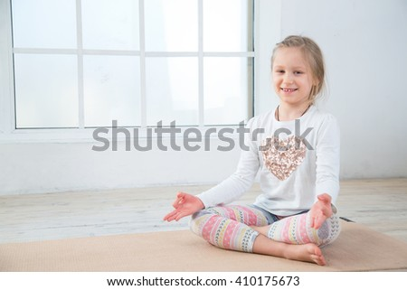 Little girl sitting in a yoga pose. Girl do yoga indoors. Child girl exercising yoga in gym near the window. - stock photo